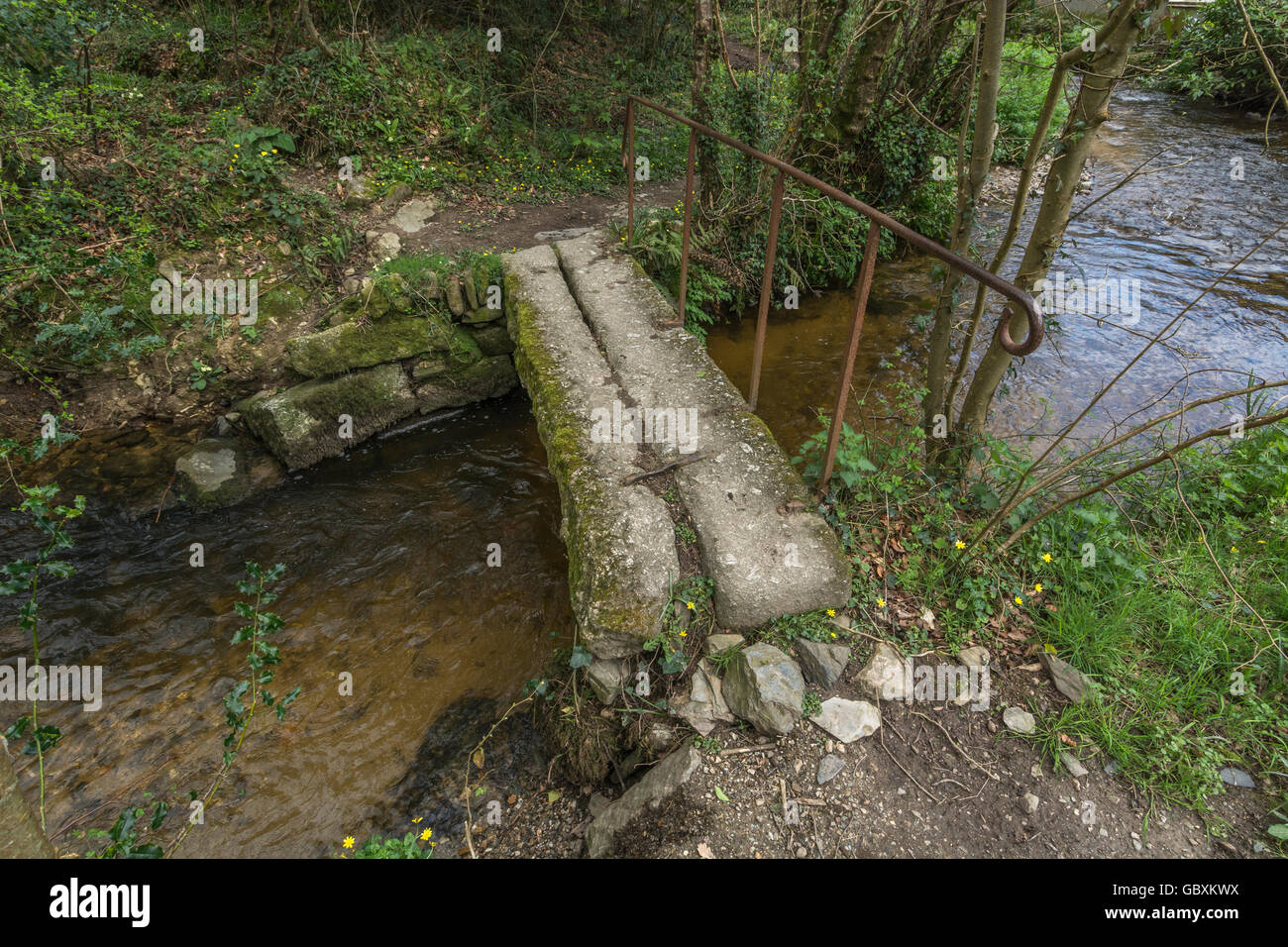 Granite stone bridge straddling a stream in mid-Cornwall. Visual metaphor for concept of uniting divided sides or - Stock Image