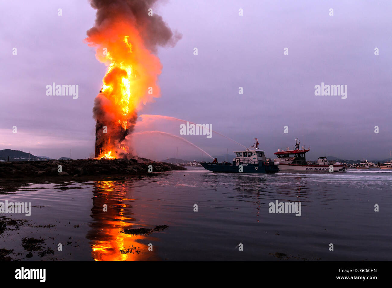 Rescue vessels safeguarding the burn down of 47,4 meter world record bonfire at Slinningen, Ålesund, Norway - Stock Image