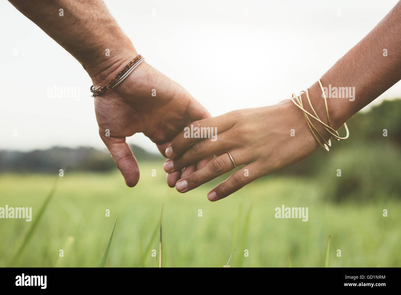 Horizontal shot of young couple walking through meadow holding hands with focus on hands . - Stock Image