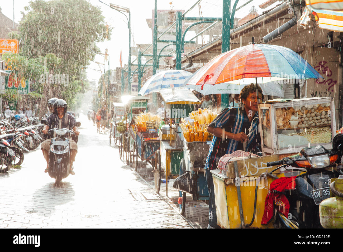 Kuta, Indonesia - March 08, 2016: Indonesian food vendor hides from the rain under umbrella of his stall on the Stock Photo
