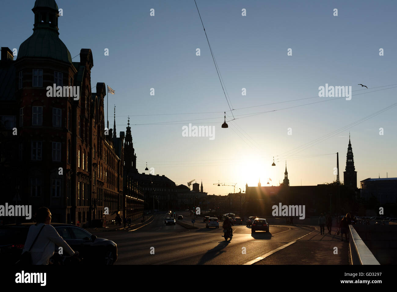 Looking towards Borsen the former stock exchange in Copenhagen Denmark with the setting sun and silhouetted buildings - Stock Image
