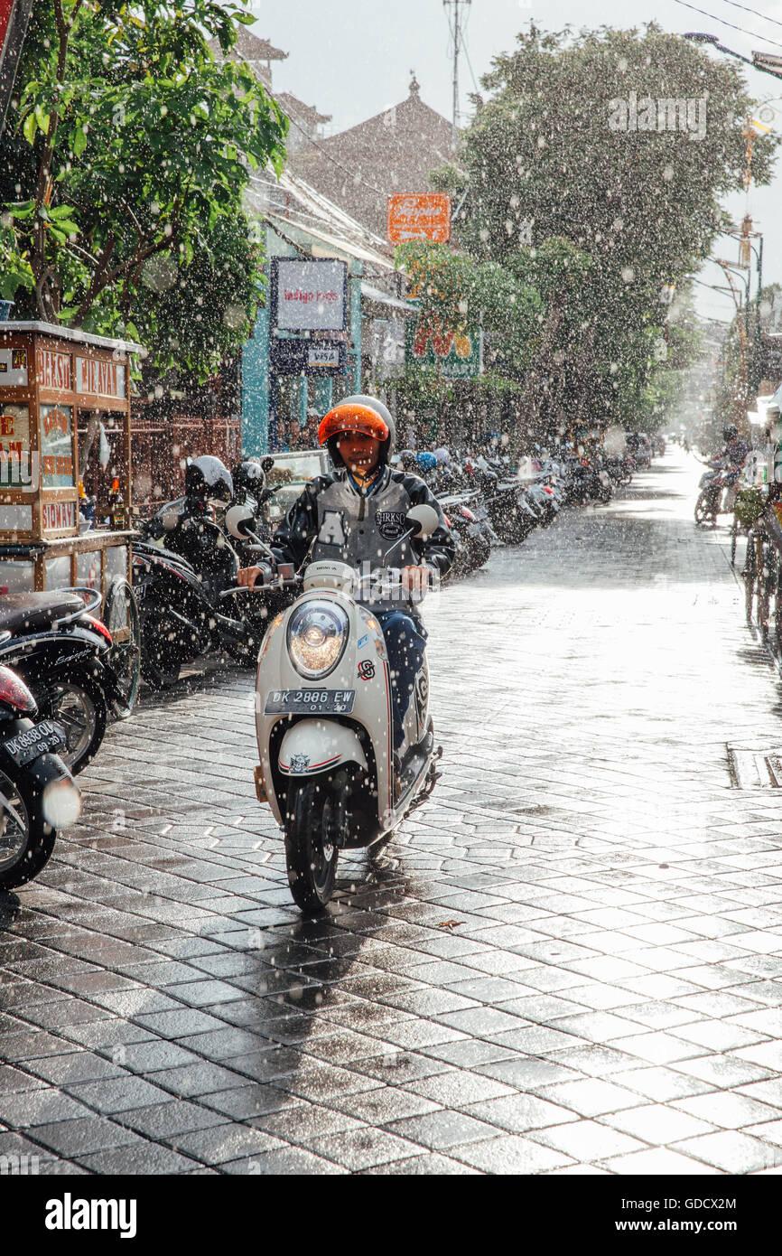 Indonesian man riding a motorbike under the rain on the street of Kuta, Bali, Indonesia. Stock Photo