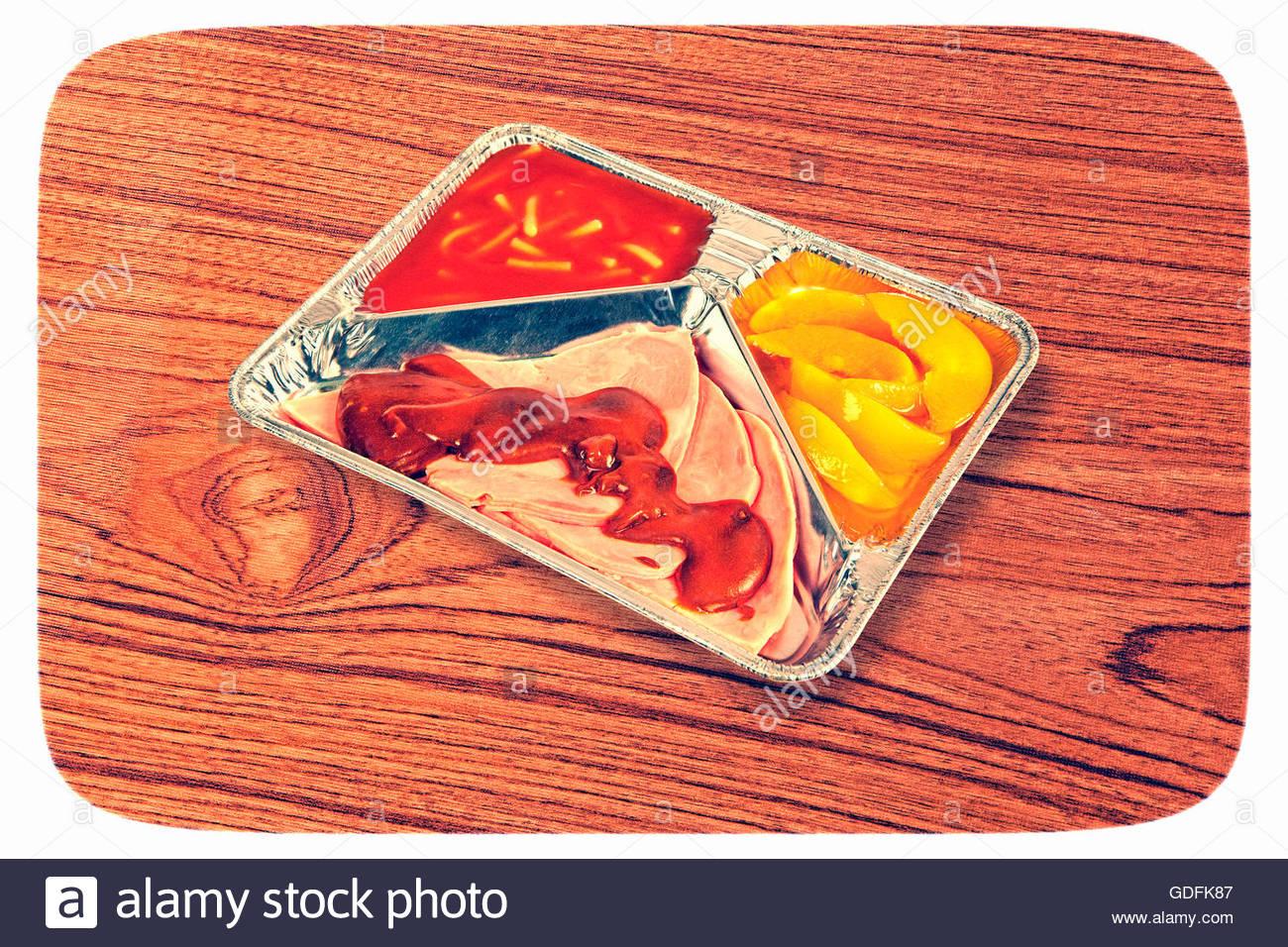 TV dinner tray vintage retro meal aluminium food dish on wooden table Stock Photo