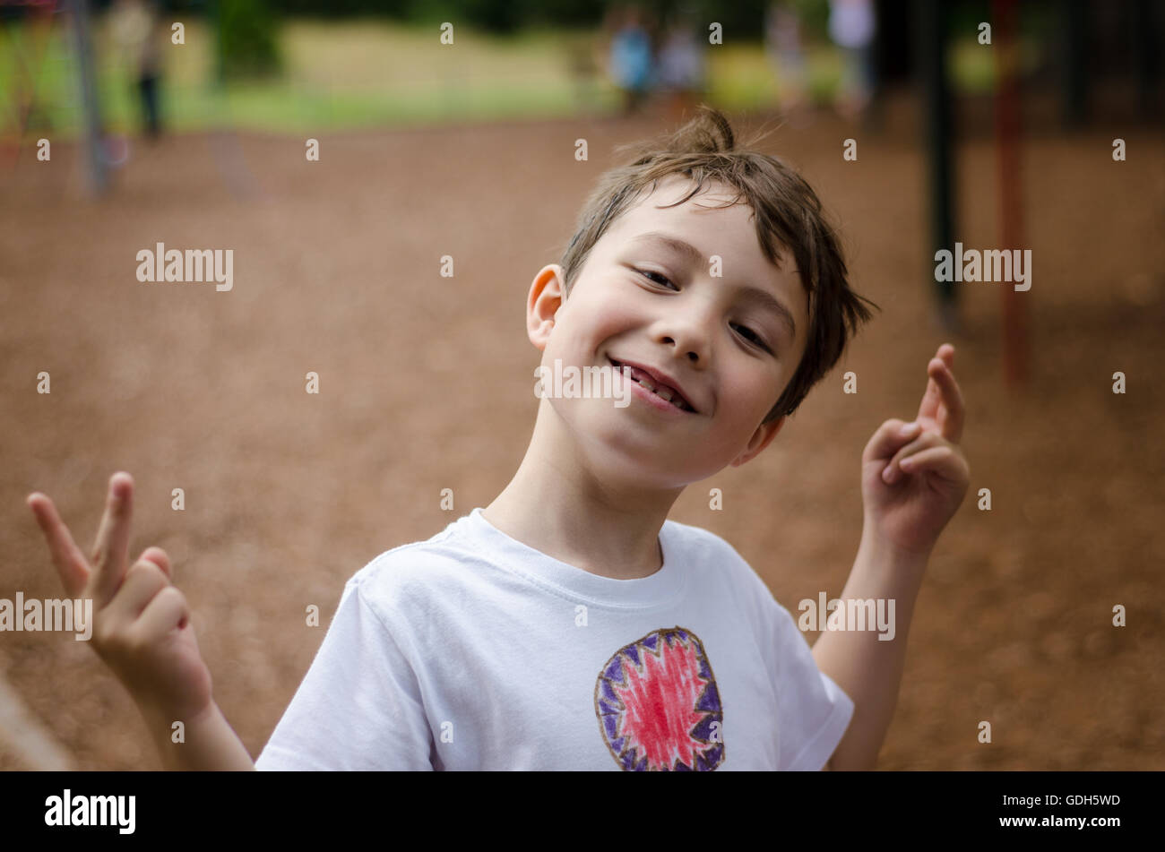 a-young-boy-poses-for-a-portrait-in-the-park-GDH5WD.jpg