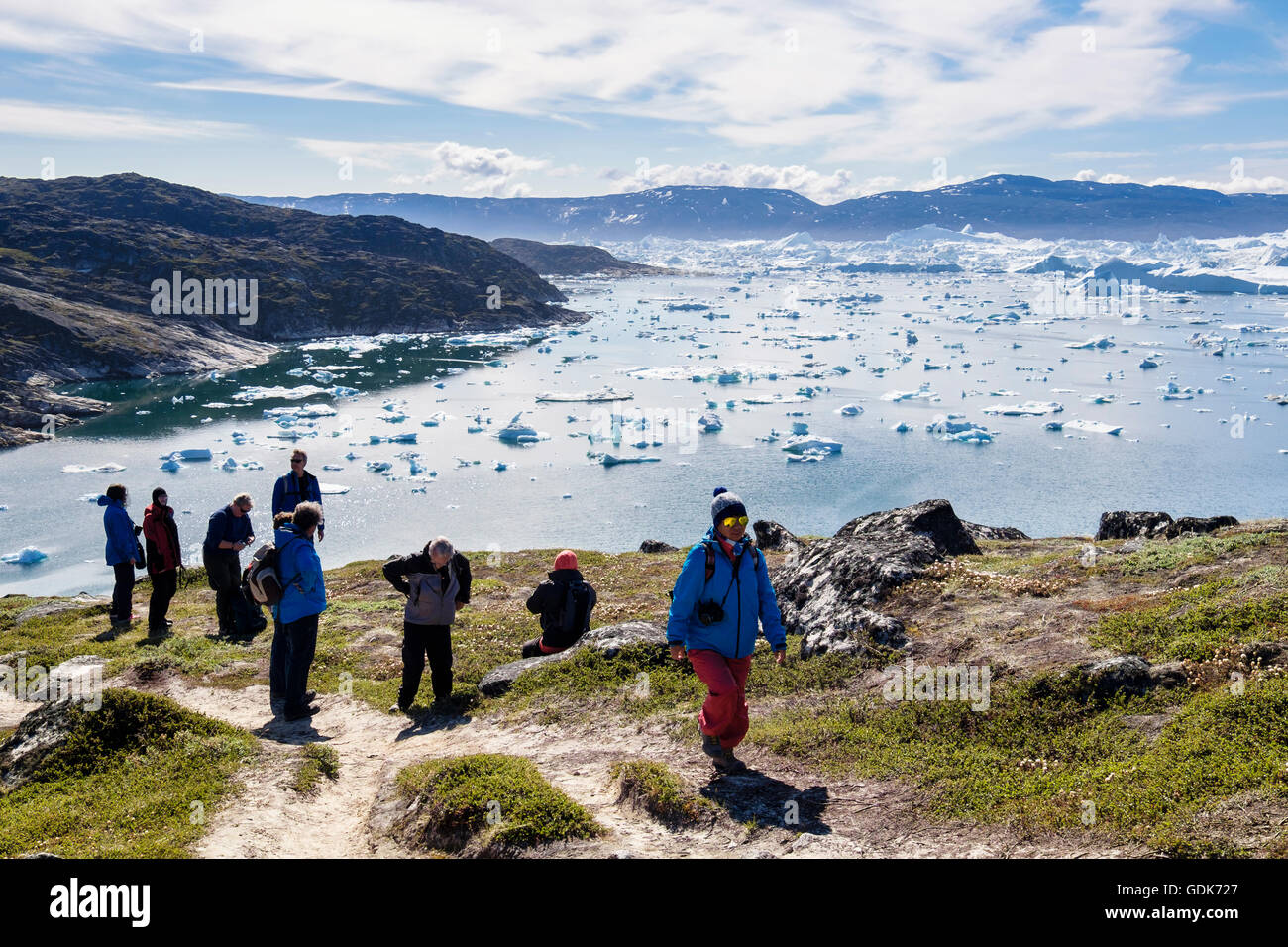 Hikers hiking on blue hike trail path by Jakobshavn or Ilulissat Icefjord with large icebergs in fjord in arctic - Stock Image