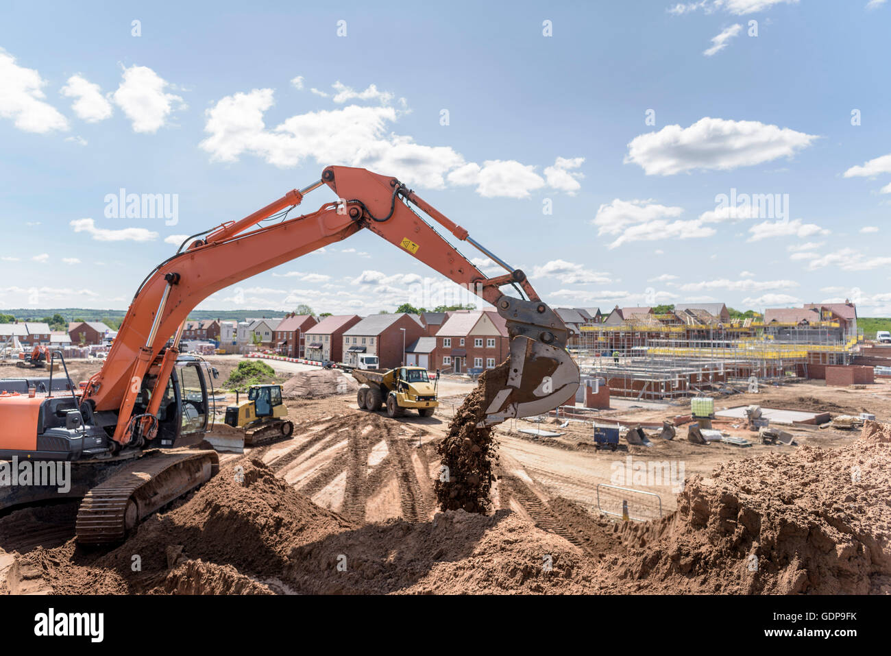 Excavator moving earth on housing building site Stock Photo
