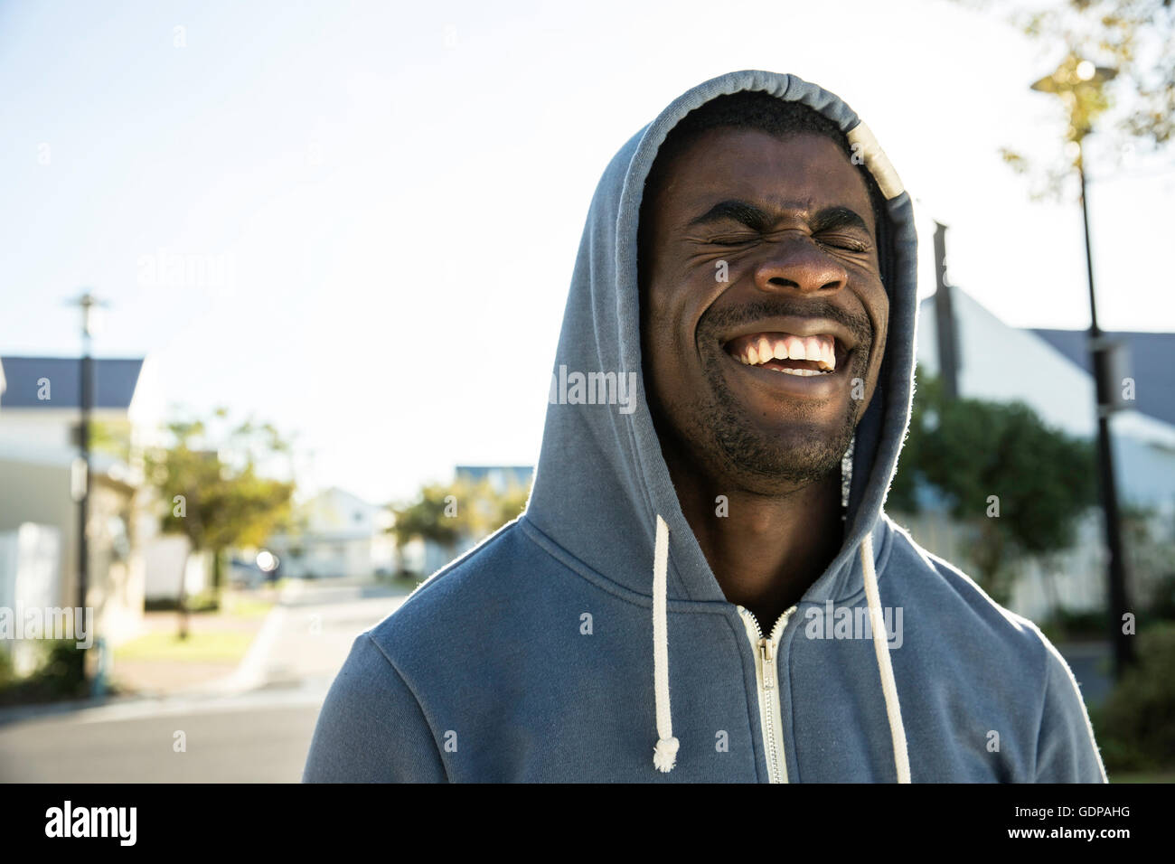 Portrait of man wearing hooded top eyes closed laughing - Stock Image