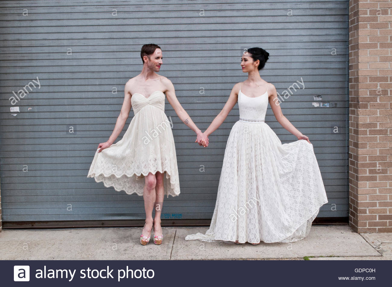 Gender fluid model and female model showing off cotton wedding dresses - Stock Image