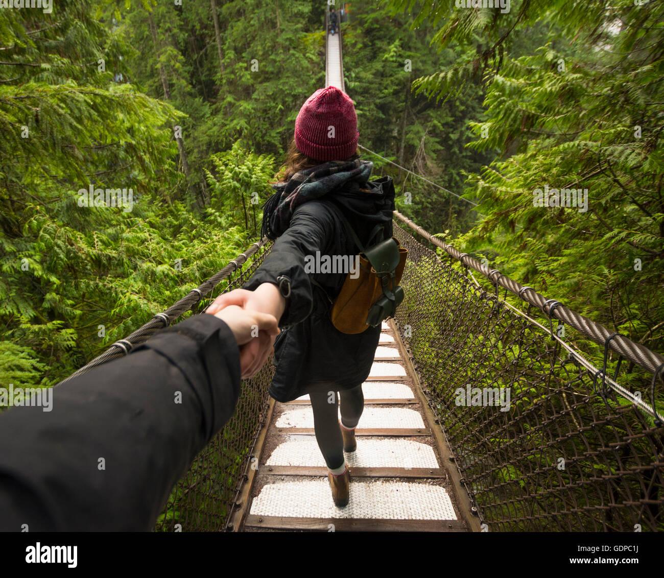 Woman on Lynn canyon suspension bridge holding mans hand, North Vancouver, British Columbia, Canada - Stock Image