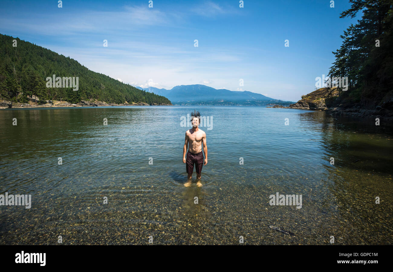 Man in ocean throwing wet hair back, Bowen Island, British Columbia, Canada - Stock Image
