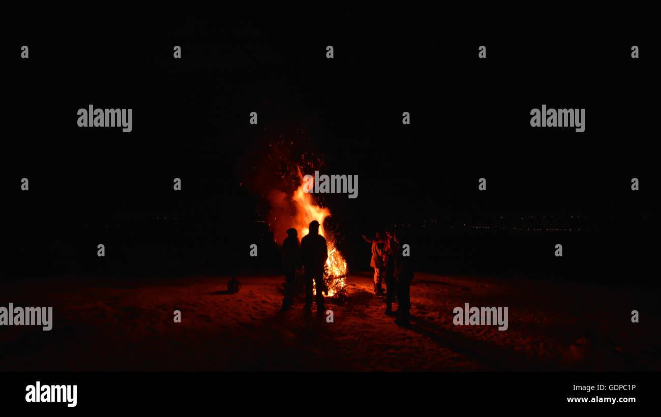 Friends in darkness around campfire, Naramata, British Columbia, Canada - Stock Image