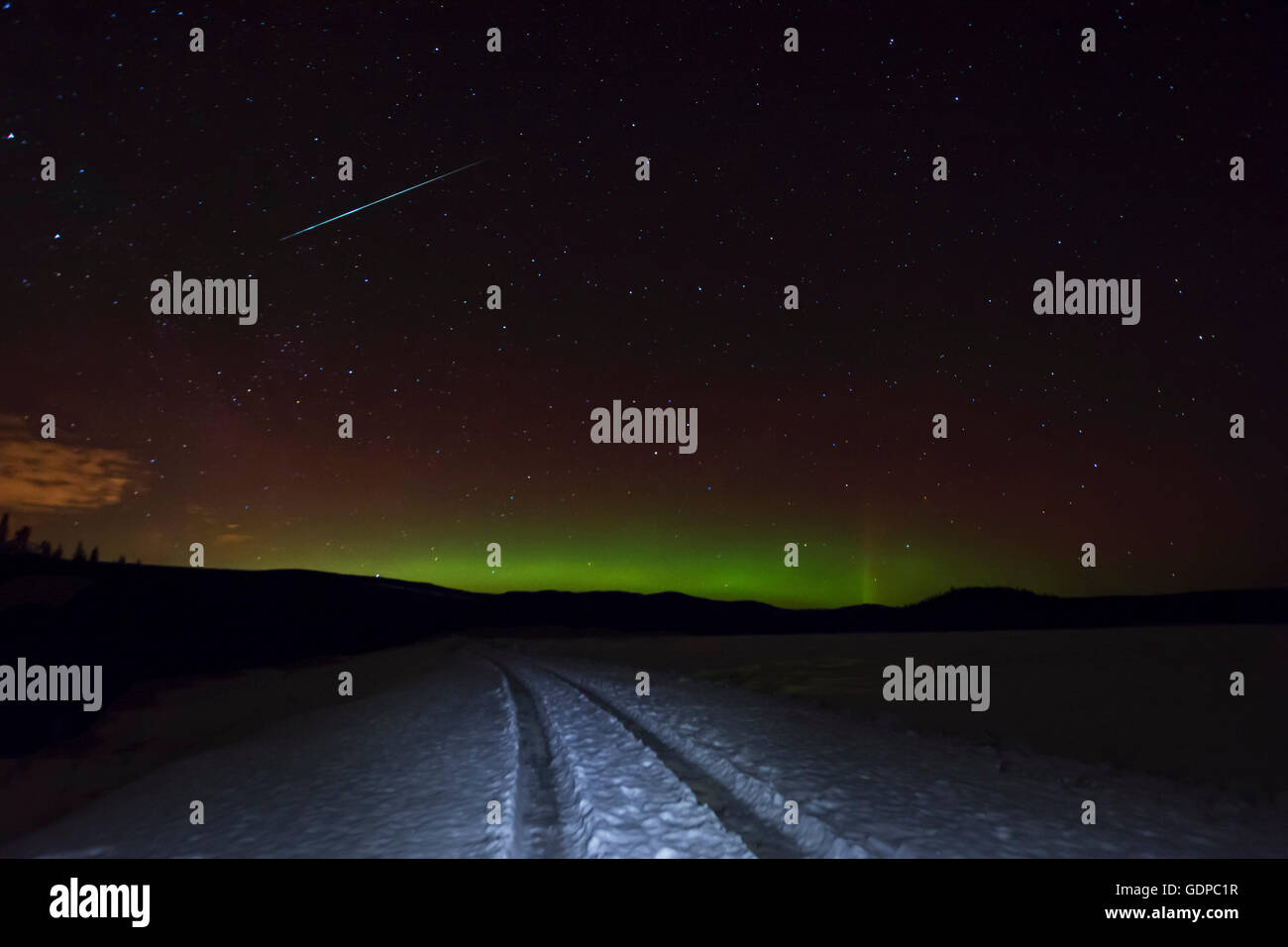 Tyre tracks in snow and aurora borealis,  Okanagan Highlands, Penticton, British Columbia, Canada - Stock Image