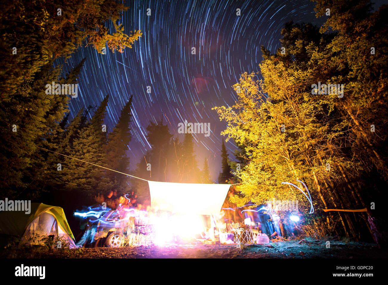 Long exposure of stars in night sky and light trails around campfire, Elinor Lake Recreational Area, Naramata, BC, - Stock Image