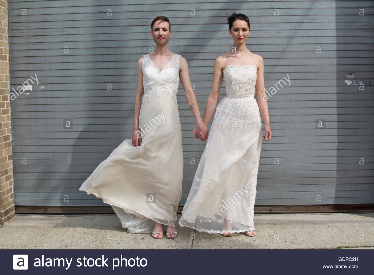 Gender fluid model and female model in couture bridal attire - Stock Image
