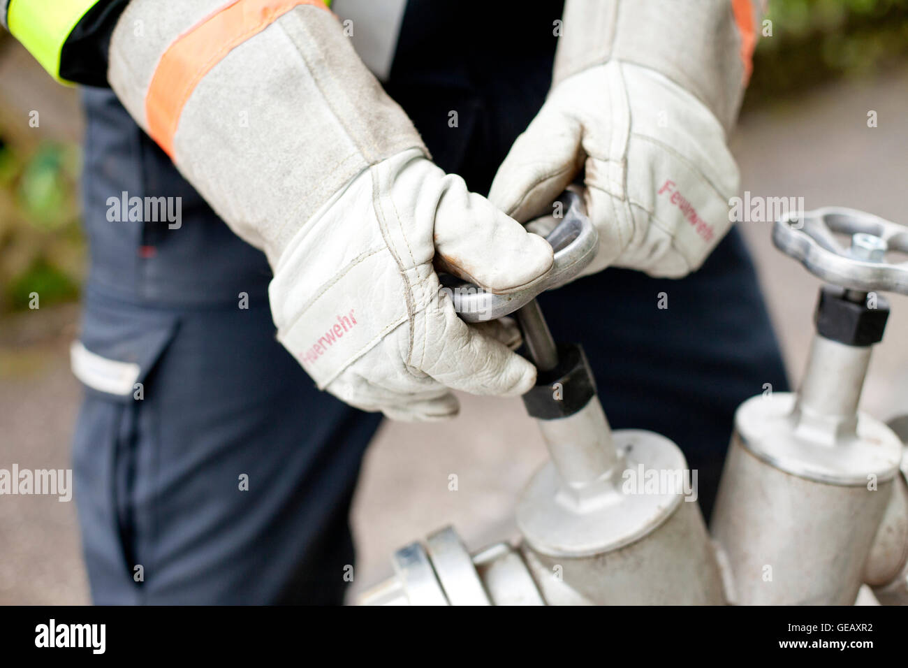 Close-up of firefighter opening fire hydrant - Stock Image