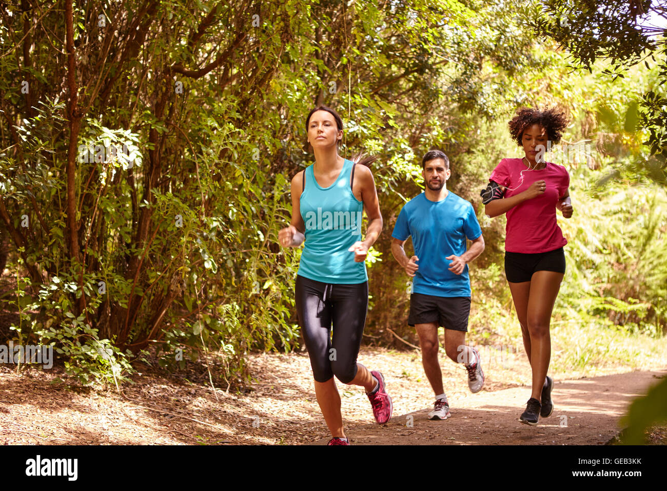 4688ed05ae35 A young guy and two girls jogging on a gravel running trail with trees  behind them while wearing t-shirts and black pants
