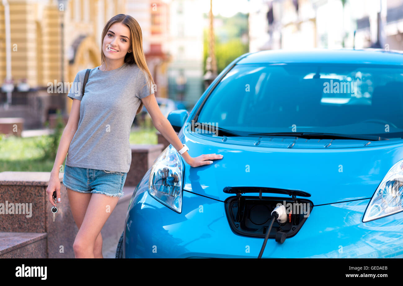 Woman standing near electric car Stock Photo