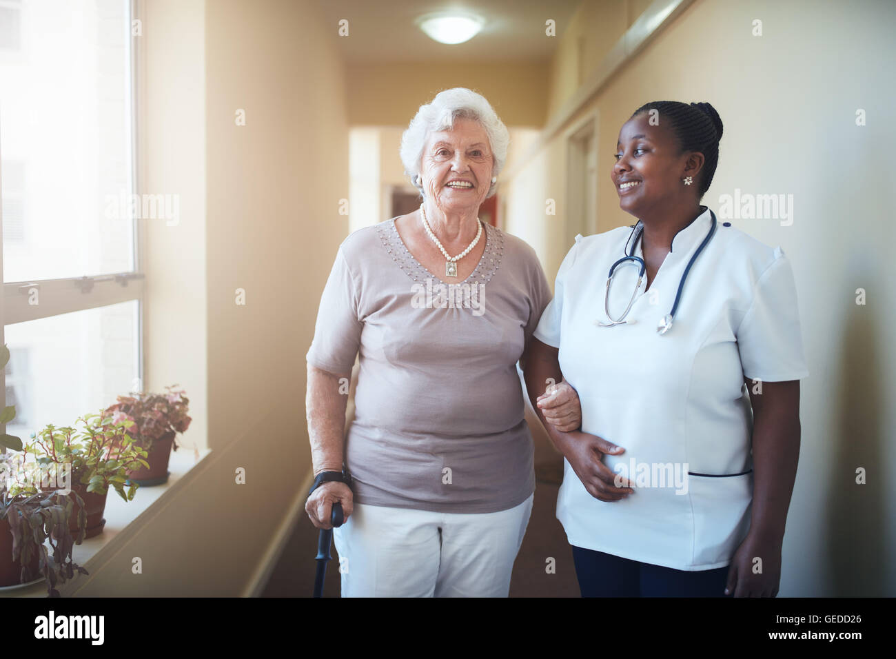 Happy healthcare worker and senior woman together at nursing home. Caring female doctor assisting a senior patient - Stock Image