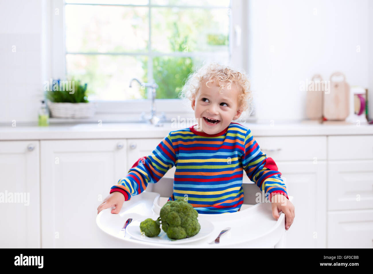 Happy baby sitting in high chair eating broccoli in a white kitchen. Healthy nutrition for kids.  sc 1 st  Alamy & Happy baby sitting in high chair eating broccoli in a white kitchen ...