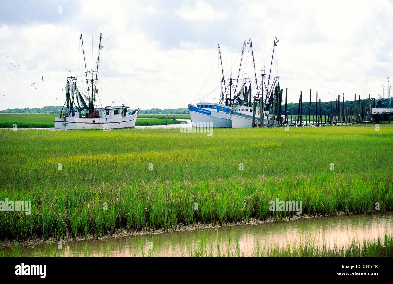 Shrimp boats navigate marshes around Hunting Island and St. Helena Island at approaches to Beaufort, South Carolina Stock Photo