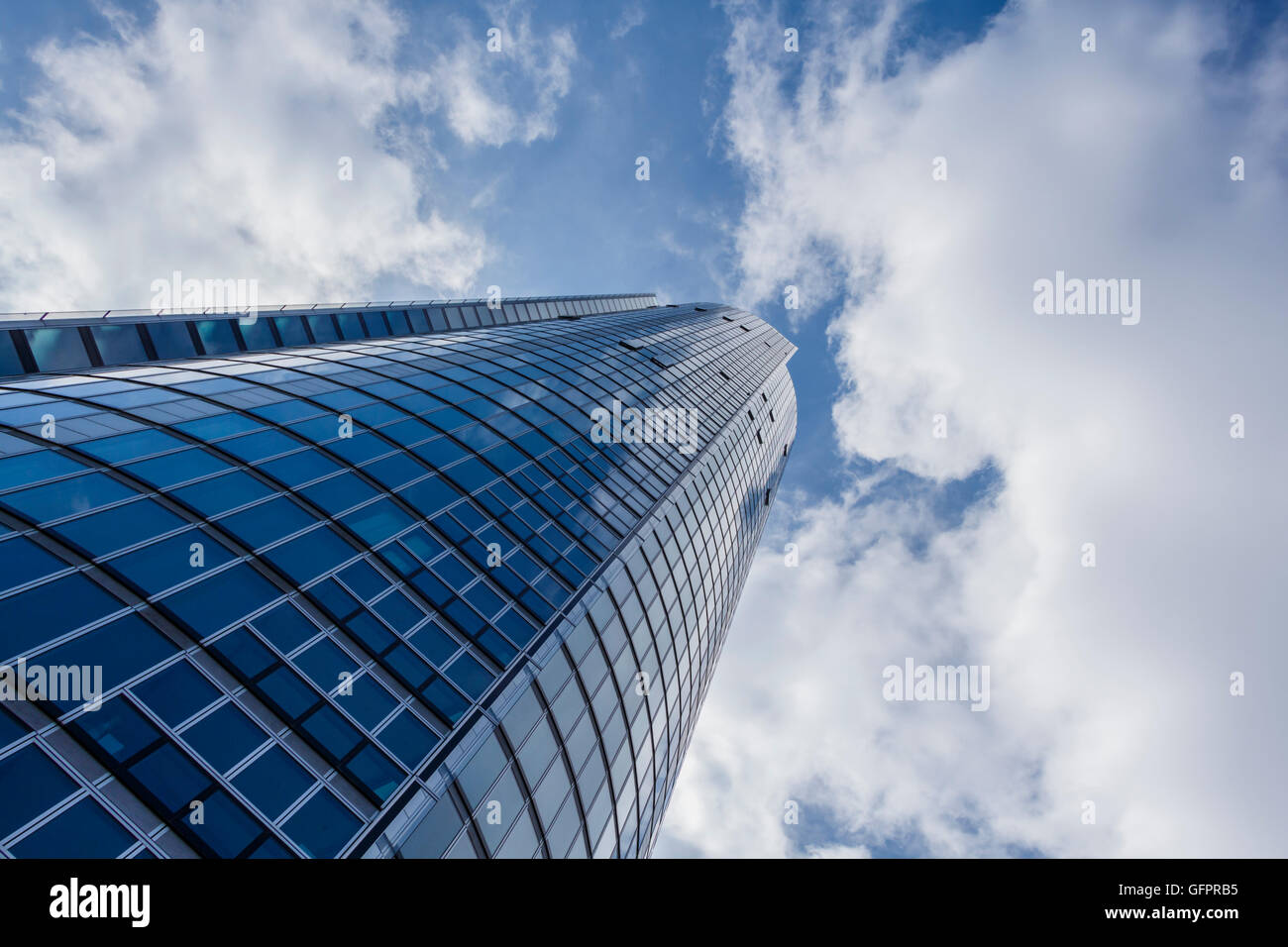 Looking up at a tall building with an cloudy sky above - Stock Image