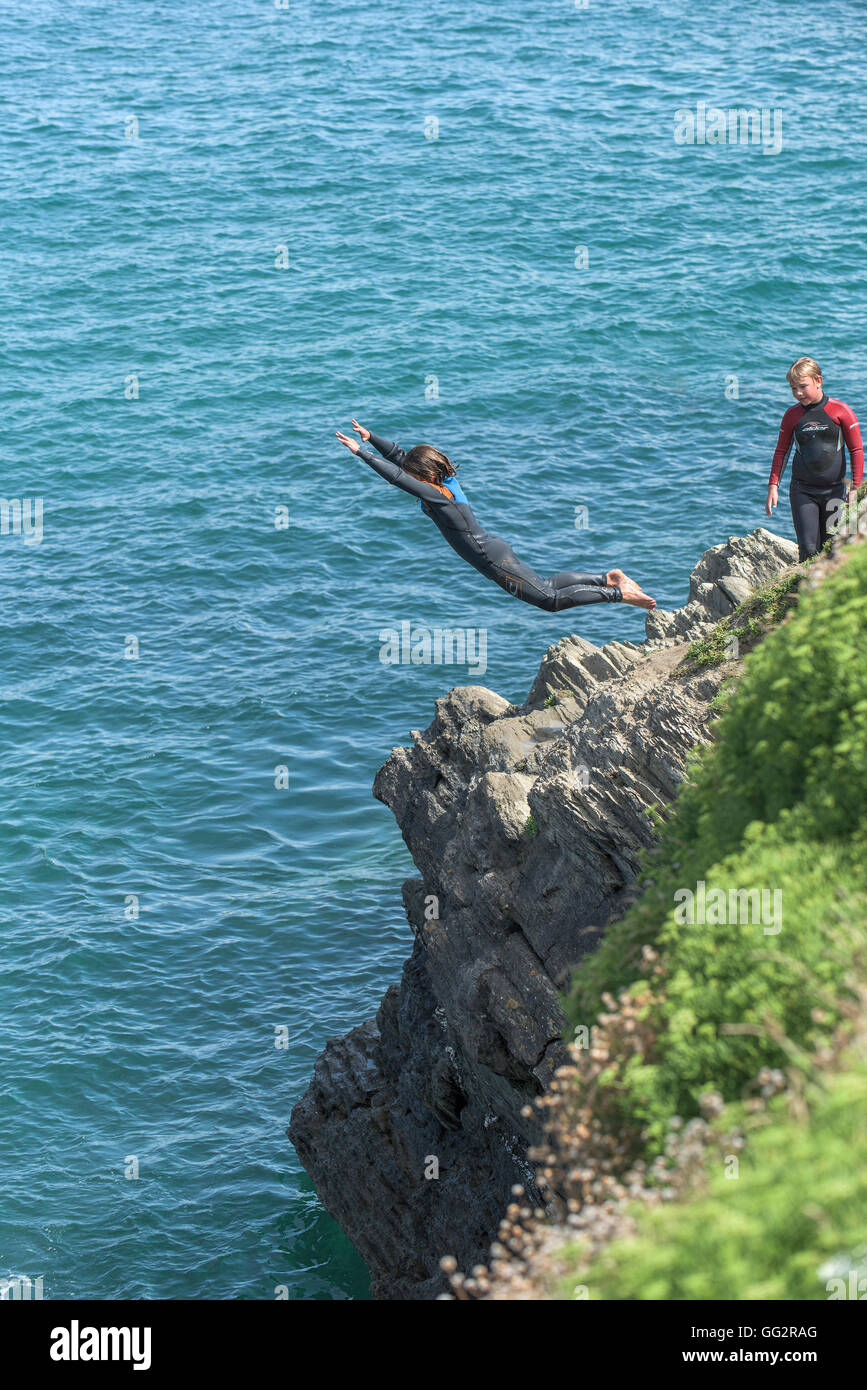 Teenagers tombstoning off cliffs in Newquay, Cornwall. - Stock Image