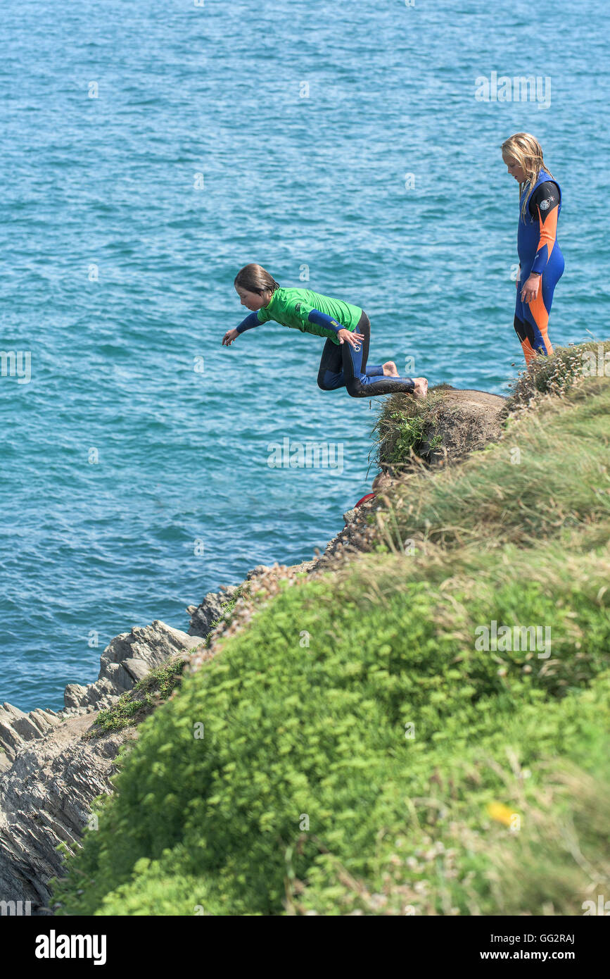 Young teenagers tombstoning off cliffs in Newquay, Cornwall. - Stock Image