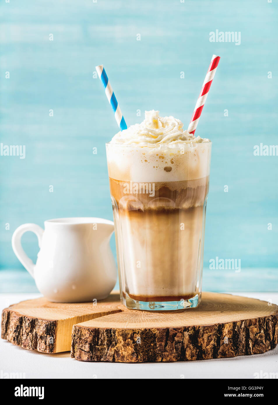 Latte macchiato with whipped cream in tall glass and pitcher on round wooden board over blue painted wall background - Stock Image