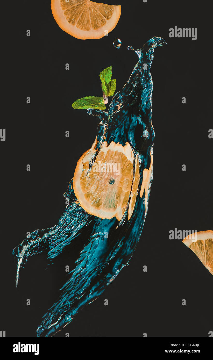 Lemon slice with a splash of water and mint leaf - Stock Image