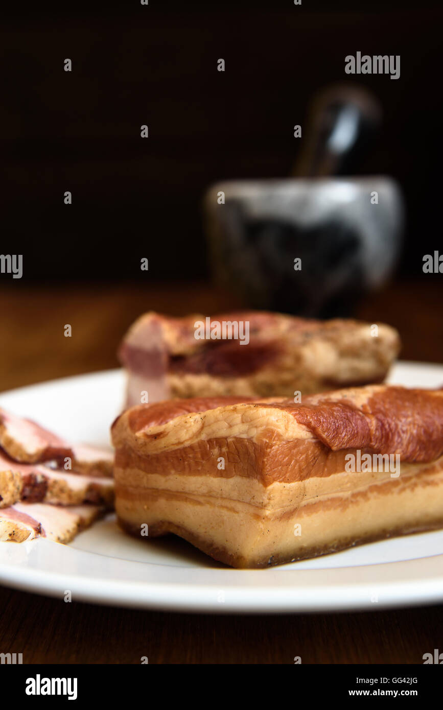 smoked pork ribs on white plate on wooden background - Stock Image