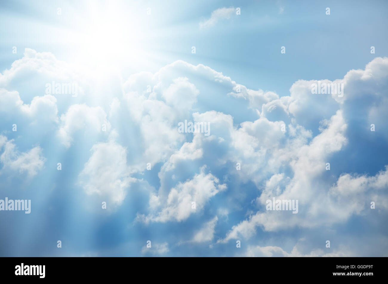 Bright sun shines among the white clouds - Stock Image