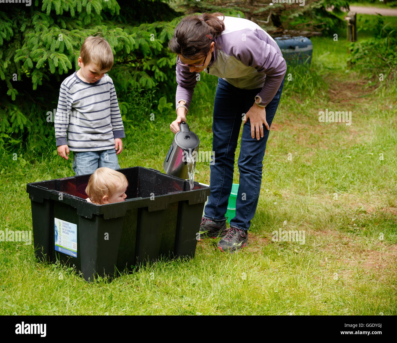 A little girl (2 years old) being bathed in a plastic box while camping Mum adds warm water from a kettle and brother Stock Photo