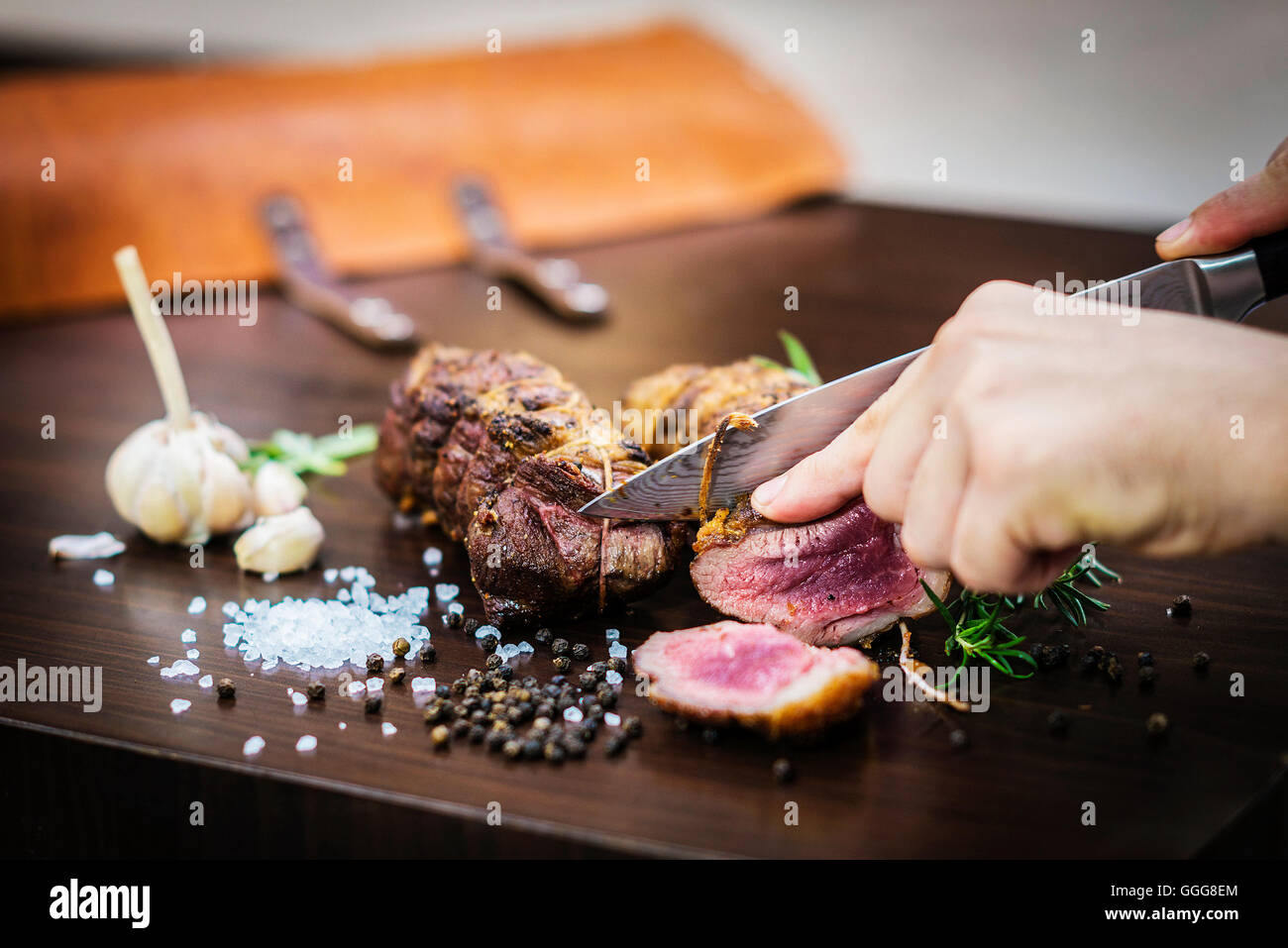 serving carving roast pork meat roll meal in rustic style with seasonings - Stock Image