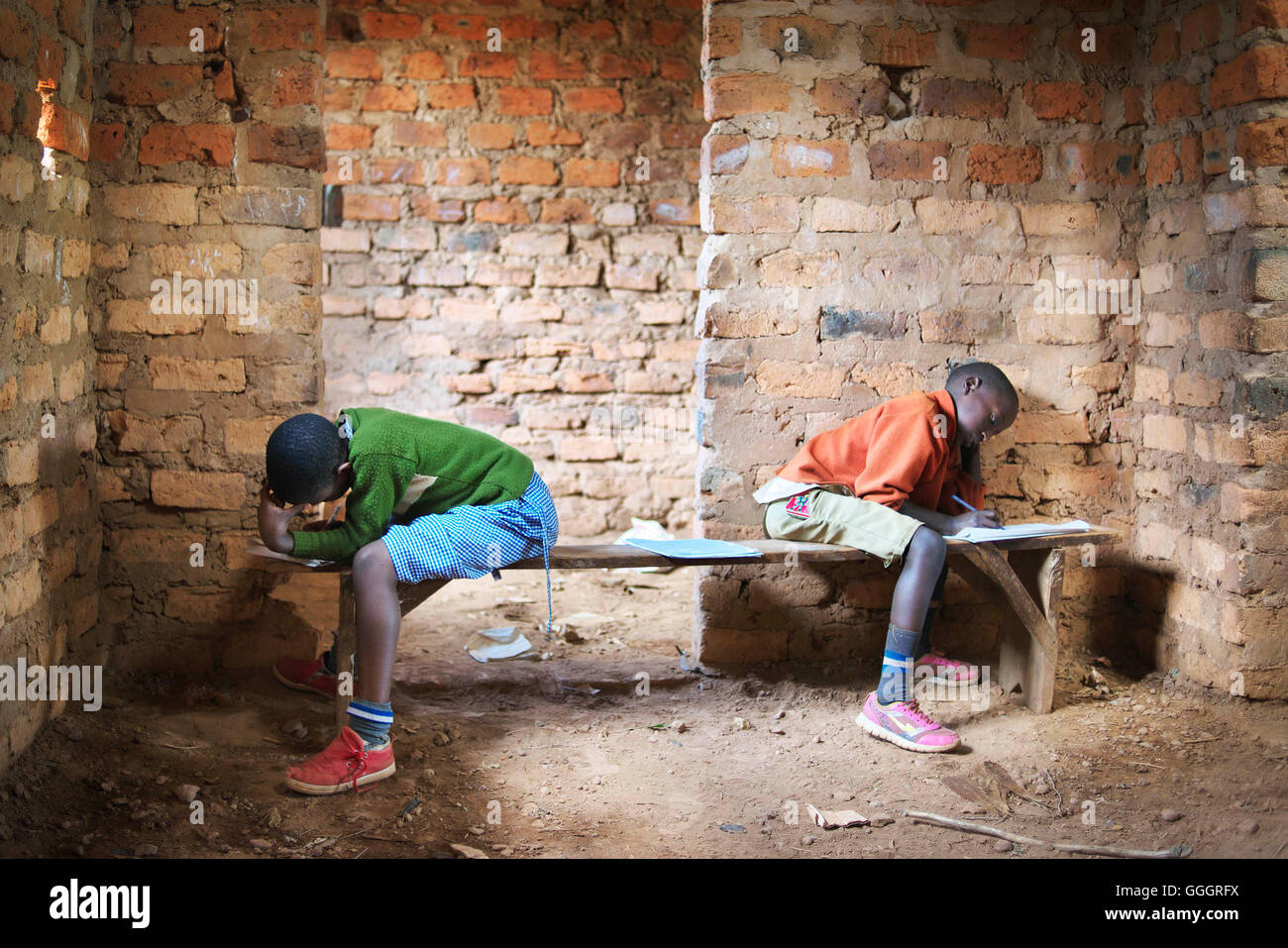 Two african school children in a rural school in Uganda/Rwanda take a school test, sitting opposite each other on - Stock Image