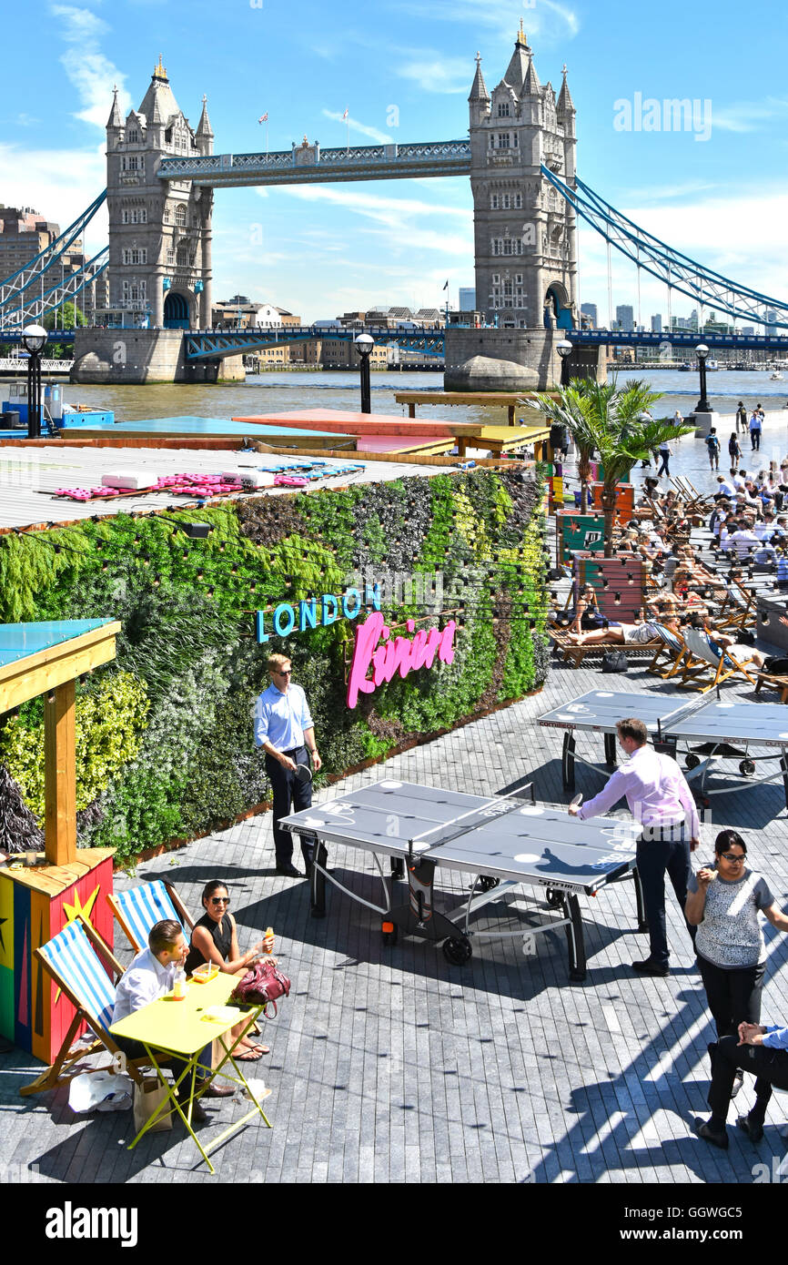 Table Tennis ping pong game in progress on the London More office complex riverside leisure areas with Tower Bridge - Stock Image