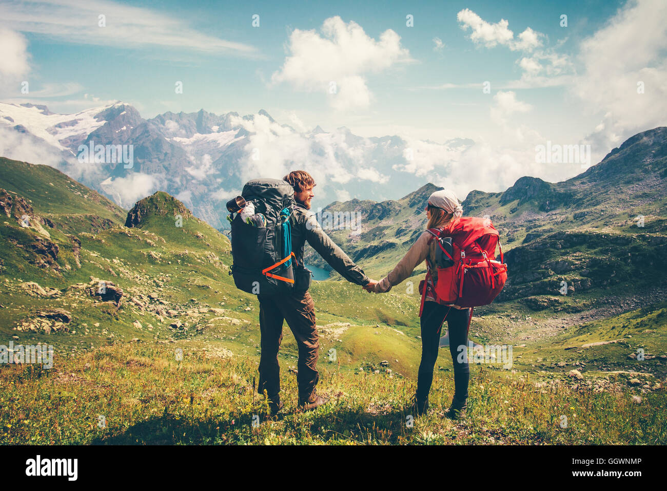 Couple Man and Woman with backpack holding hands mountaineering Travel Lifestyle summer vacations concept mountains - Stock Image