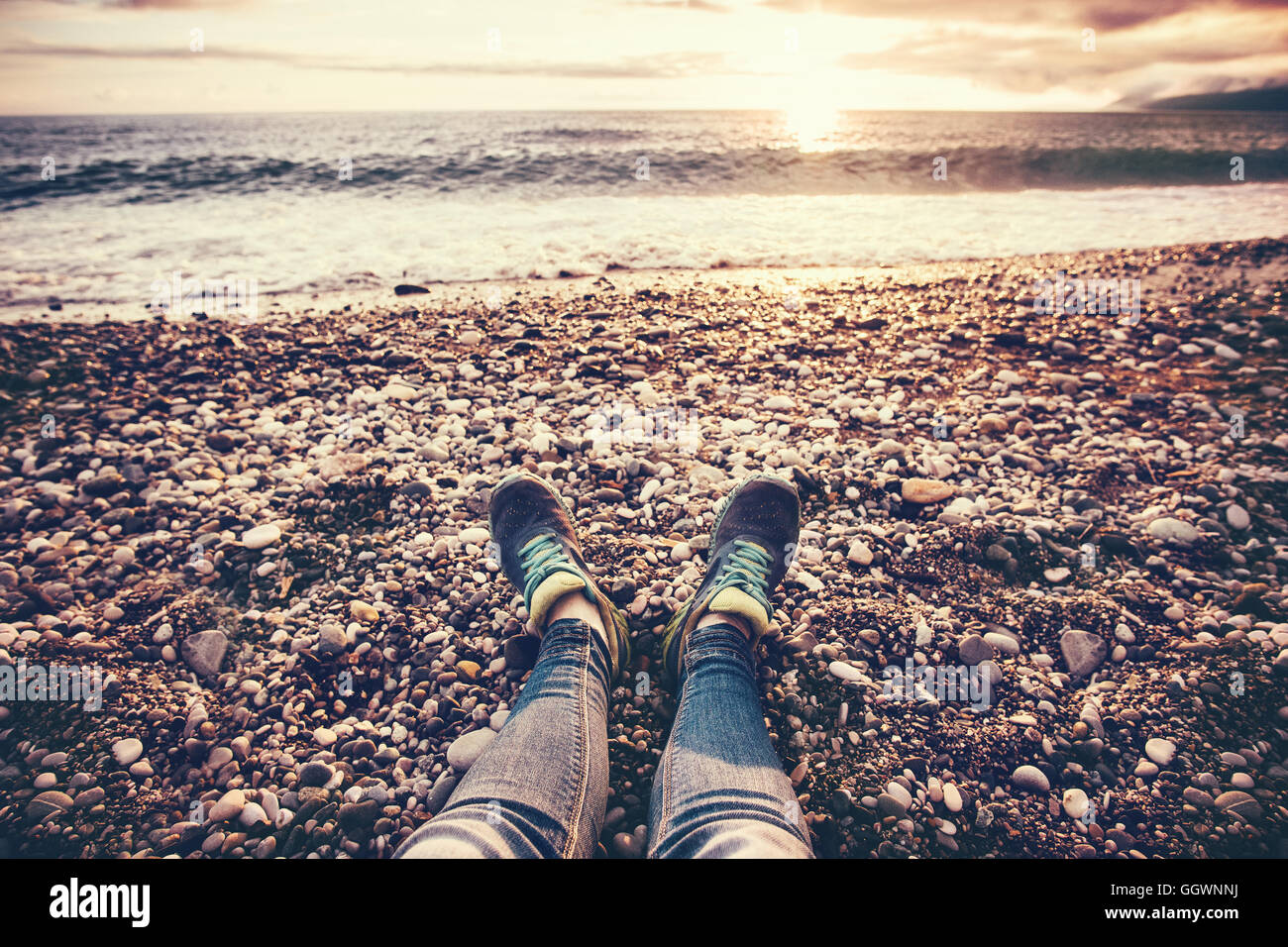 Woman Feet sneakers on beach sea sunset Travel Lifestyle Summer vacations trendy concept - Stock Image