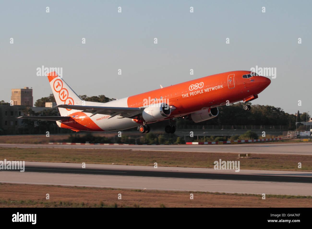 TNT Airways Boeing 737-400F cargo jet plane taking off from Malta - Stock Image