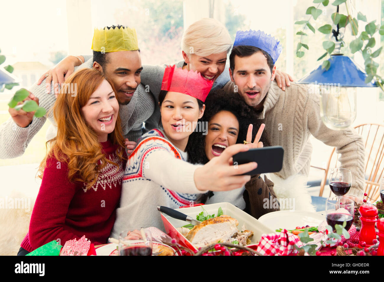 15c2dcfc6a468 Friends wearing paper crowns taking selfie at Christmas dinner Stock ...