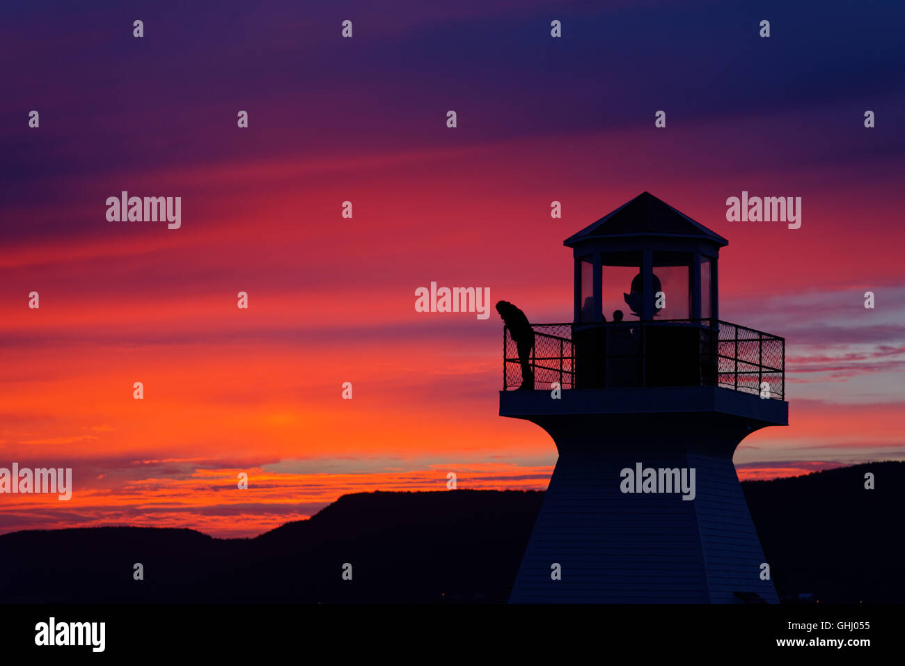 A person stood at the top of a lighthouse, silhouetted against a fiery sunset in Carleton Gaspesie Quebec Canada Stock Photo
