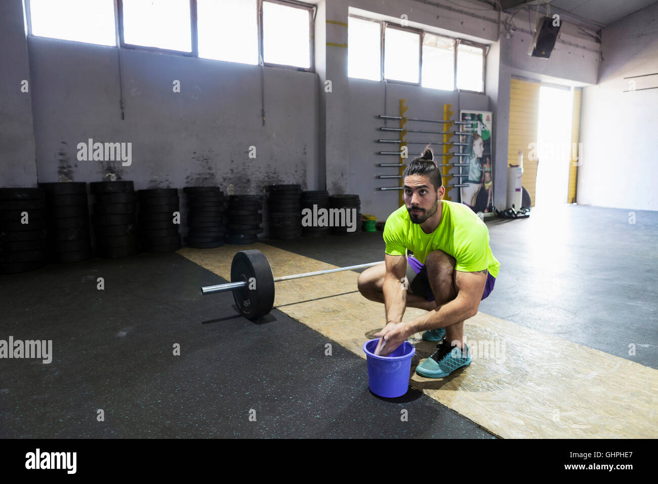 Athlete in gym prepares for weightlifting - Stock Image