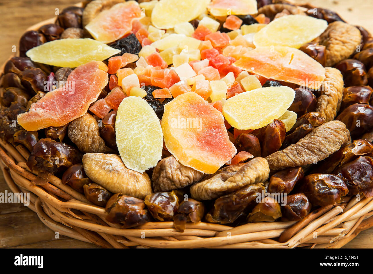 Dried and candied fruits assortment in a wicker tray - Stock Image
