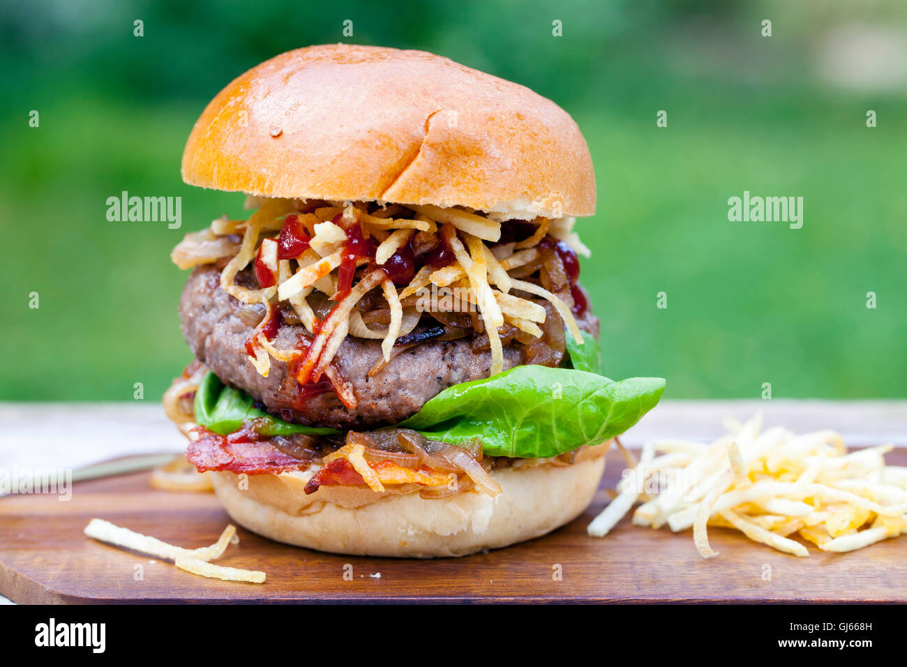 Beefburger with fried onions, bacon and string fries in brioche bun - Stock Image