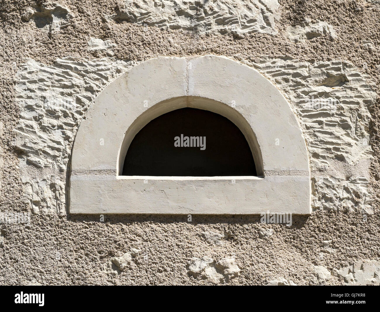 New semi-circular window opening in wall of old stone house - France. - Stock Image
