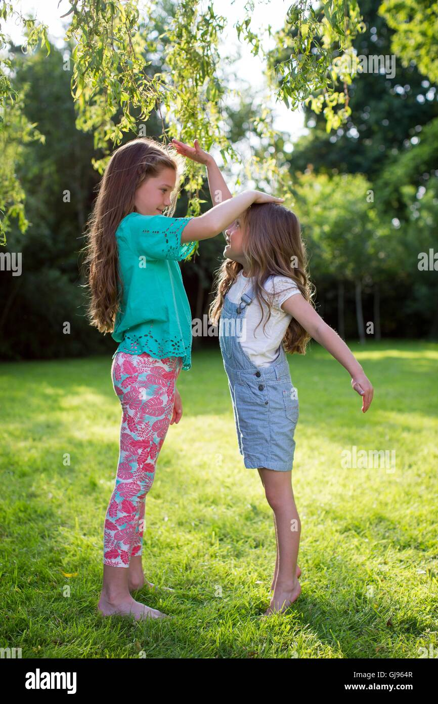 PROPERTY RELEASED. MODEL RELEASED. Two sisters measuring their height against each other. - Stock Image