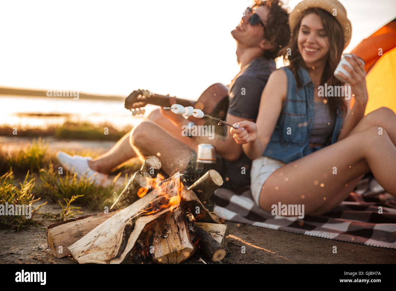 Cheerful beautiful young couple playing guitar and frying marshmallows on bonfire - Stock Image