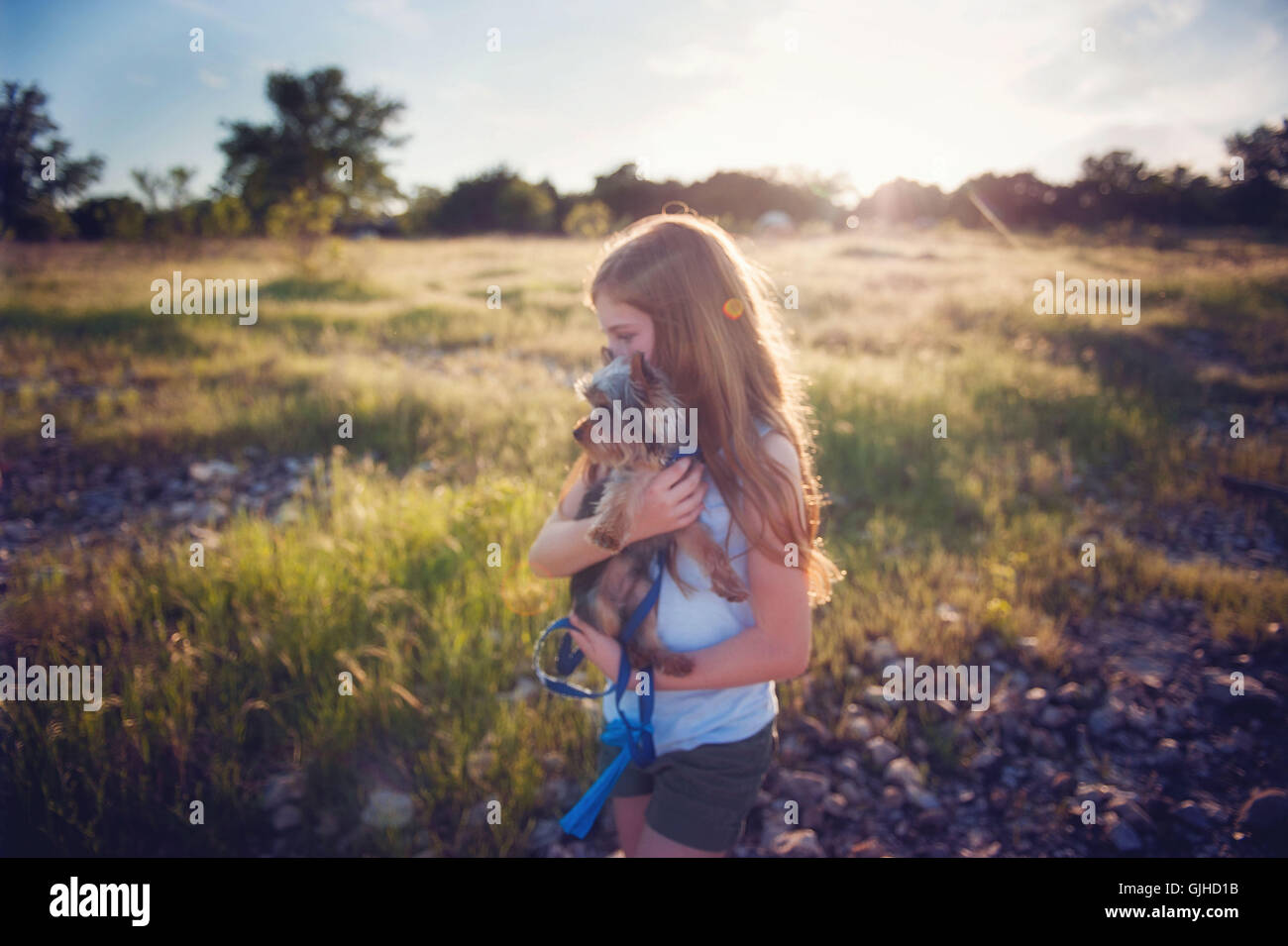 Girl carrying her dog on hike - Stock Image