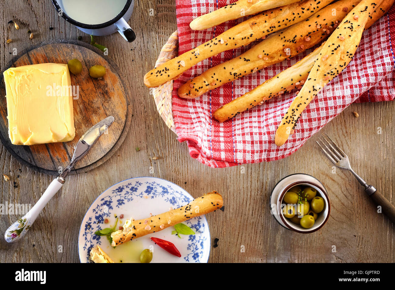 Bread sticks with butter, breakfast setting on a wooden table. - Stock Image