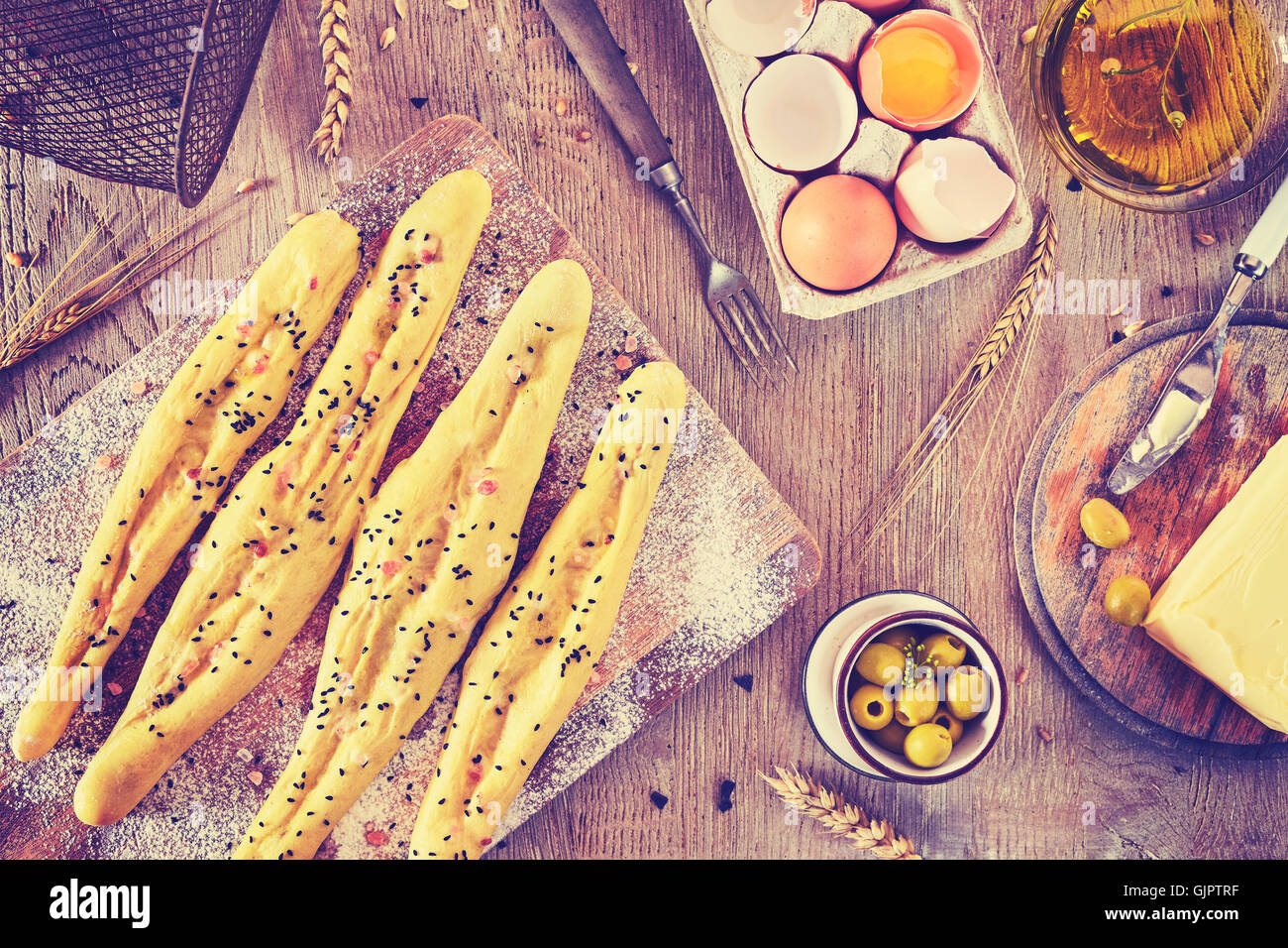 Vintage toned bread sticks ready for baking, rustic setting on a wooden table. - Stock Image