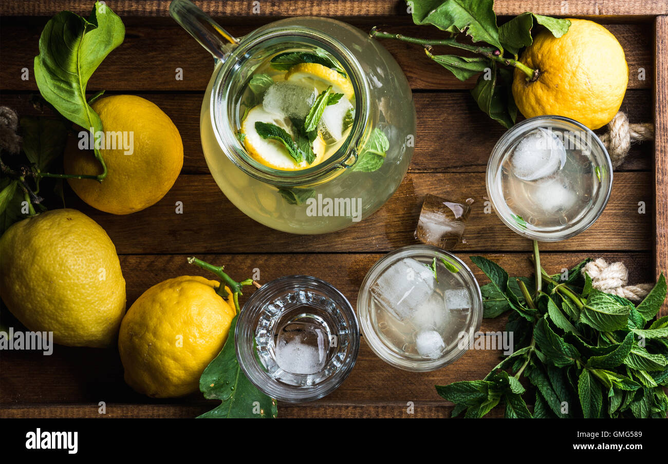 Homemade mint lemonade served with fresh lemons and ice over wooden background - Stock Image